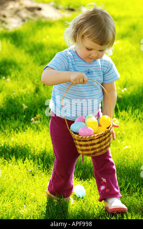 Two year old girl holding basket full of easter eggs - Stock Photo