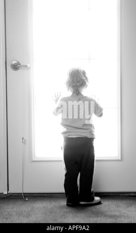 Young girl looking out window - Stock Photo