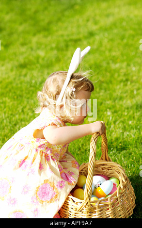 Two year old girl holding easter basket wearing bunny ears - Stock Photo
