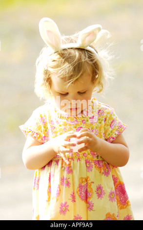 Two year old girl wearing bunny ears opening easter egg - Stock Photo