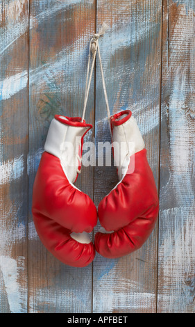 A Pair of Boxing Gloves Hanging from a Nail - Stock Photo