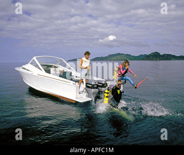 SCUBA divers enter the water from a dive boat over a coral reef near Qamea Island Fiji - Stock Photo