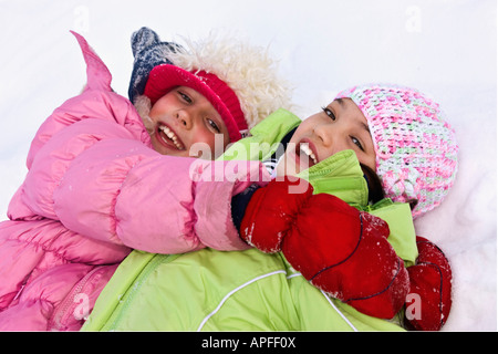 Girls laying in the snow - Stock Photo