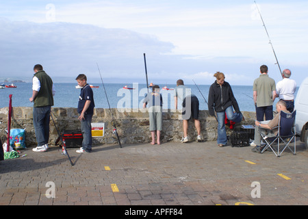 Anglers busy fishing in the sea from the harbour wall at Tenby Pembrokeshire Wales Britain GB UK - Stock Photo