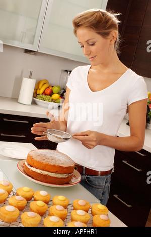 WOMAN BAKING CAKES IN KITCHEN - Stock Photo