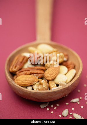 Selection of nuts and seeds on a wooden spoon on dark purple background - Stock Photo