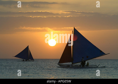 Sailboats at sunset off of White Beach in Boracay, Philippines. - Stock Photo