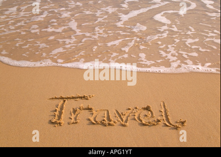 Travel written in sand on the shoreline of a golden sandy beach - Stock Photo