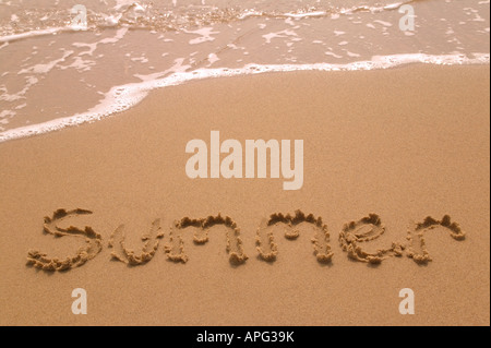 Summer written in golden sand on the shoreline as the waves come in - Stock Photo