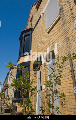 Empty House Boarded Up With Metal Shutters Over Windows On