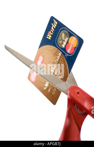 Scissors cutting a credit card indicating bad credit consumer debt and overspending - Stock Photo