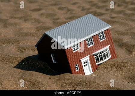 Toy model house sinking in sand - Stock Photo