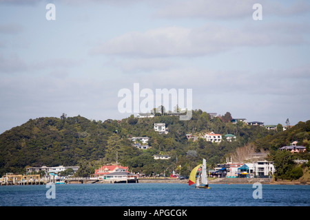 Paihia Bay of Islands Northland North Island New Zealand View of town and coastline across water with yacht sailing - Stock Photo