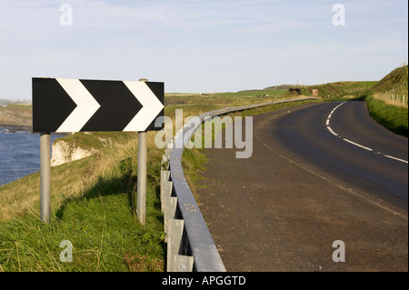 black and white chevron sharp deviation to the right road sign near dangerous bend on cliffs on the A2 coast road - Stock Photo