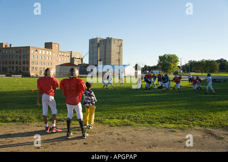 WISCONSIN Racine Two boys in football uniforms watching game in field junior high students playing - Stock Photo
