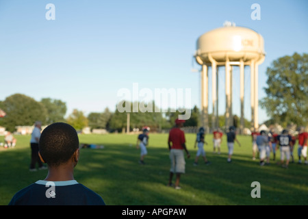 WISCONSIN Racine African American boy watching football game in field junior high students playing water tower in - Stock Photo