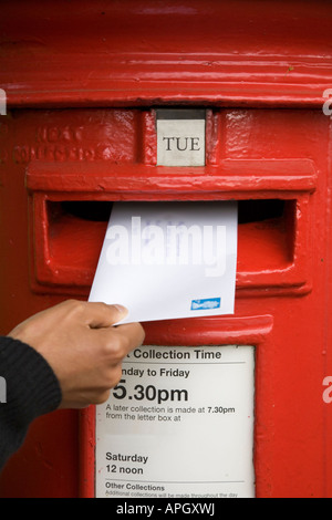A woman posts a letter in a traditional British red post box - Stock Photo