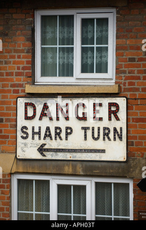 A house protected on a sharp bend by a large sign 'danger sharp turn'. Picture by Jim Holden - Stock Photo