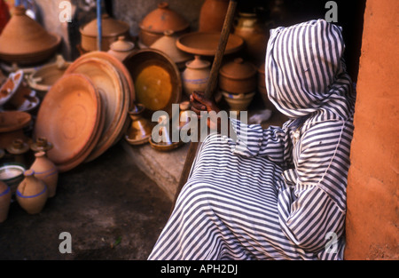 A local man in a striped djelaba rests on his journey through the labyrinth of shops and stalls in the souks of - Stock Photo