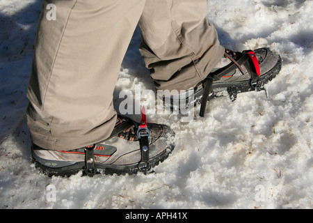 Adjustable boot crampons for walking on icy frozen snow in the mountains Bavaria Germany Europe - Stock Photo