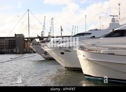 View across the bow of three yachts moored up at the London Boat Show - Stock Photo