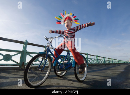 A small boy in a Red Indian headdress shouting as he plays on a trike on the cycle lane on Brighton seafront - Stock Photo