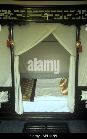 Very grand four poster bed in a bedroom of the Lusong Yuan Hotel on Banchang Hutong Street in Beijing - Stock Photo
