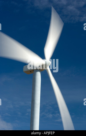 The blades of a wind turbine spin against a blue sky in an energy producing blur - Stock Photo