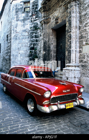 Cuba Havana La Habana Habana Vieja Red old American 50 s car parked on cobbled street in the old town yellow licence - Stock Photo