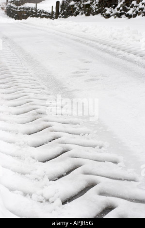 PEAT LANE, BEWERLEY, NIDDERDALE, N YORKS. 14th March 2006. After a snowfall, farmers leave tractor tyre tread pattern - Stock Photo
