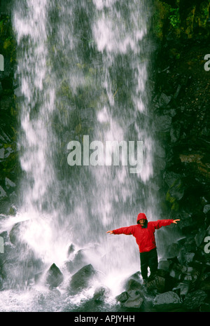 Carl Galvin in a red Mountain Equipment gore tex jacket under Svartifoss Waterfall in Iceland - Stock Photo