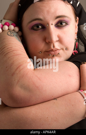 young punk goth welsh woman: arms scarred and marked from self harming with razor blade; she has multiple facial - Stock Photo