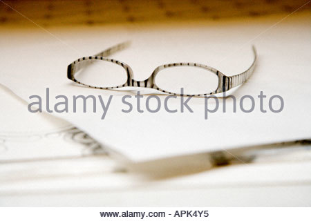 fashionable reading glasses laying on a piece of blank white paper - Stock Photo