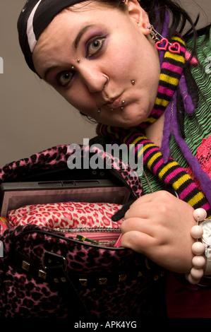 young chubby punk woman with pierced face showing the contents of her handbag - Stock Photo