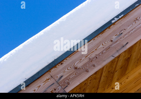 Thick snow of the roof of a luxury wooden chalet detail in the ski resort of Saas Fee in Switzerland - Stock Photo