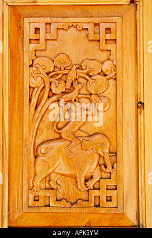 Carved wooden door depicting the four friends at Likir Gompa buddhist monastery in Ladakh India - Stock Photo