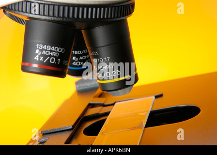 Close up of a microscope in a research lab showing the objective lenses and a slide - Stock Photo