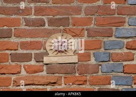Metal sun sign with a number perhaps an old insurance company symbol on the brick wall of a house - Stock Photo