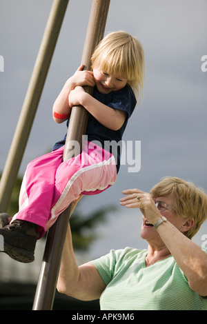 4 year Old Girl Sliding Down a Post at a Playground With Grandma - Stock Photo