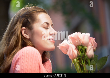 Young woman smelling roses (profile) - Stock Photo