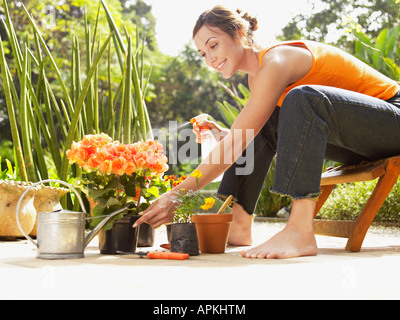 Young woman spraying water on flowers (low angle view) - Stock Photo