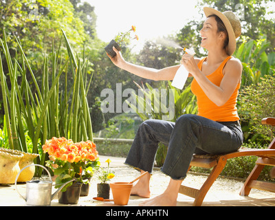 Young woman spraying water on flowers - Stock Photo