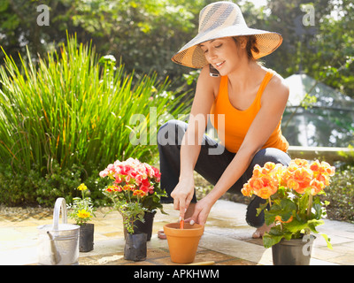 Young woman planting flowers and talking on cell phone - Stock Photo