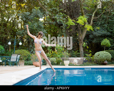 Young woman dipping toe in swimming pool - Stock Photo