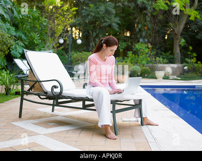 Young woman using laptop by swimming pool - Stock Photo