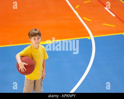 Boy holding basket ball (portrait, high angle view) - Stock Photo