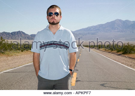 Young man standing on empty road. - Stock Photo