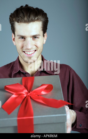 Young man holding a gift - Stock Photo