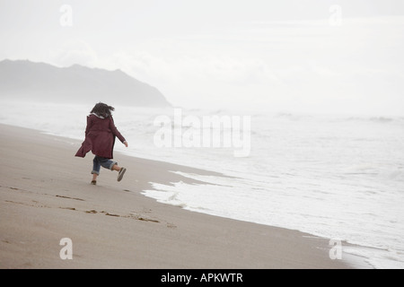 Woman running on sandy beach (rear view) - Stock Photo