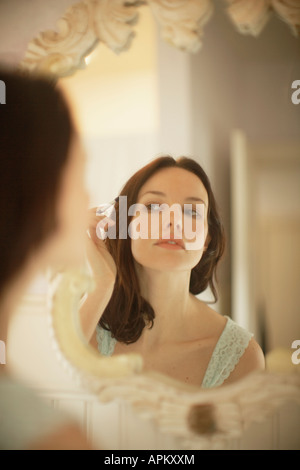 Woman applying make-up in front of mirror - Stock Photo